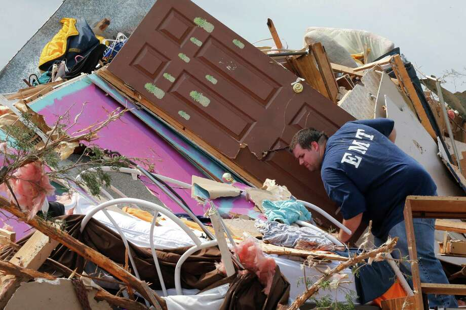 A resident who did not want to give his name, searches through the rubble of his mobile home in the Steelman Estates Mobile Home Park, destroyed by Sunday's tornado, near Shawnee, Okla., Monday, May 20, 2013. The tornado that slammed into Oklahoma on Sunday is now blamed for two deaths. Authorities say two men in their 70s have been found dead in or near a mobile home park outside of Shawnee. (AP Photo Sue Ogrocki) Photo: Sue Ogrocki, Associated Press / AP