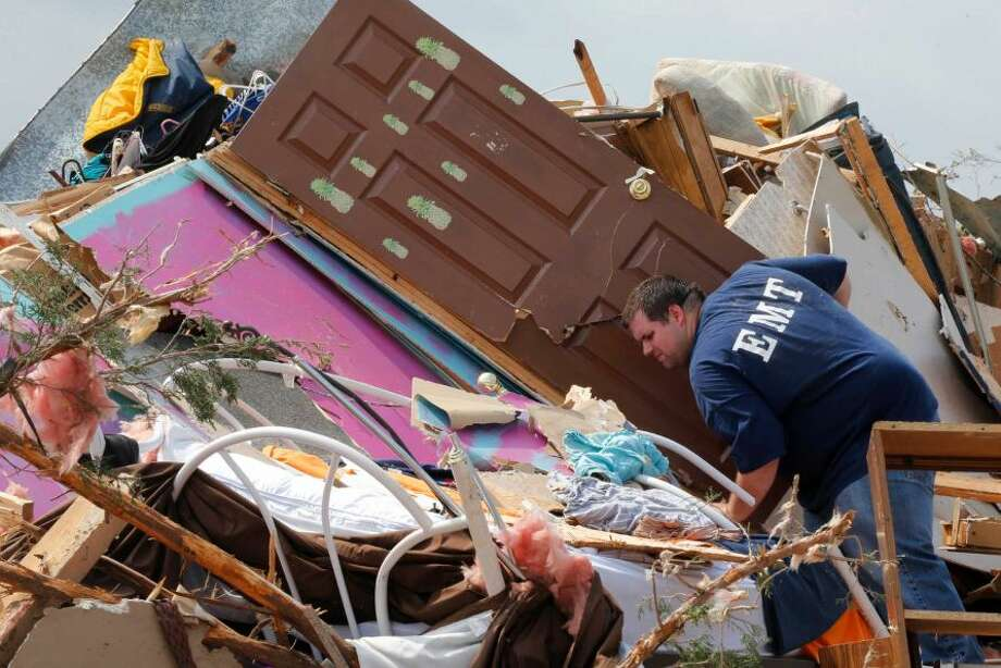 A resident who did not want to give his name, searches through the rubble of his mobile home in the Steelman Estates Mobile Home Park, destroyed by Sunday's tornado, near Shawnee, Okla., Monday, May 20, 2013. The tornado that slammed into Oklahoma on Sunday is now blamed for two deaths. Authorities say two men in their 70s have been found dead in or near a mobile home park outside of Shawnee