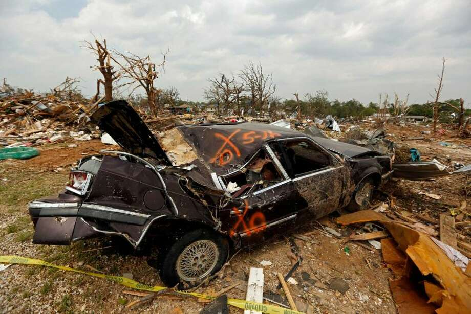 A smashed car sits in a debris field in the Rancho Brazos subdivision Sunday, May 19, 2013 in Granbury, Texas. Residents in the neighborhood continued cleanup of their damaged homes after a May 15 tornado wreaked havoc on the area, injuring dozens and killing six people.