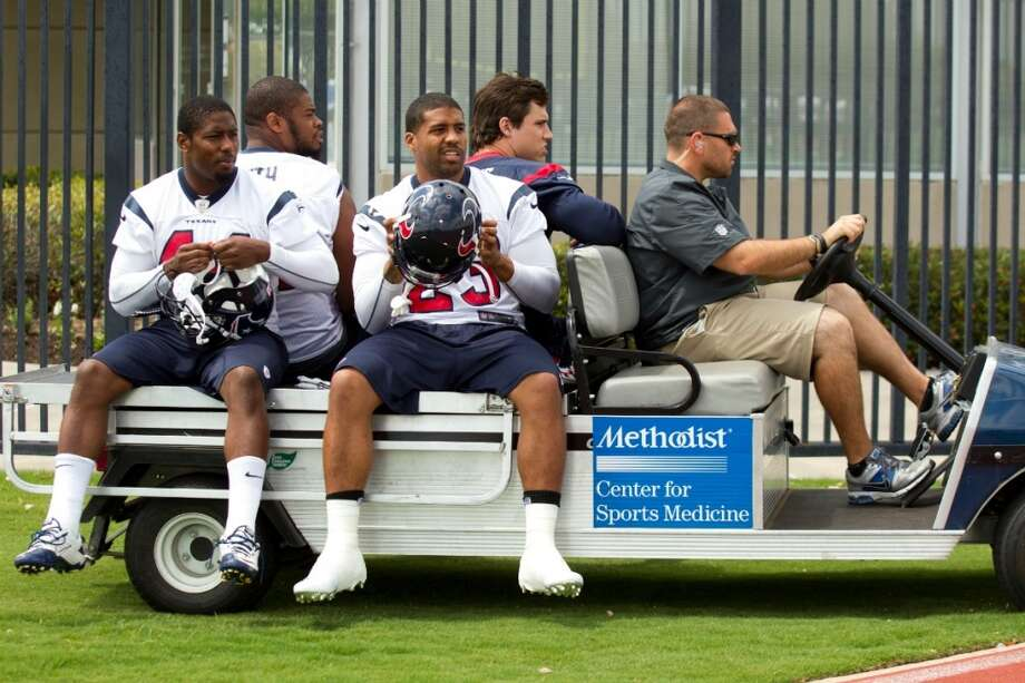 Ben Tate (44), Arian Foster (23), Wade Smith and Brian Cushing take a ride to practice.
