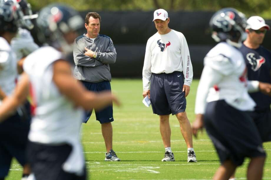 Texans head coach Gary Kubiak, left, and offensive coordinator Rick Dennison watch warm ups at the beginning of practice,