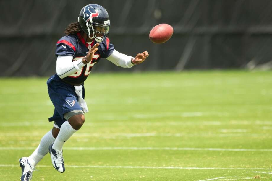 Texans safety D.J. Swearinger flips a ball back to a coach during a drill.