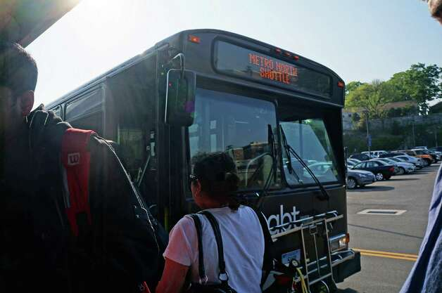Passengers get off shuttle buses Monday afternoon at the downtown train station, while others board for the trip back to Westport to catch a westbound train. Photo: Genevieve Reilly / Fairfield Citizen