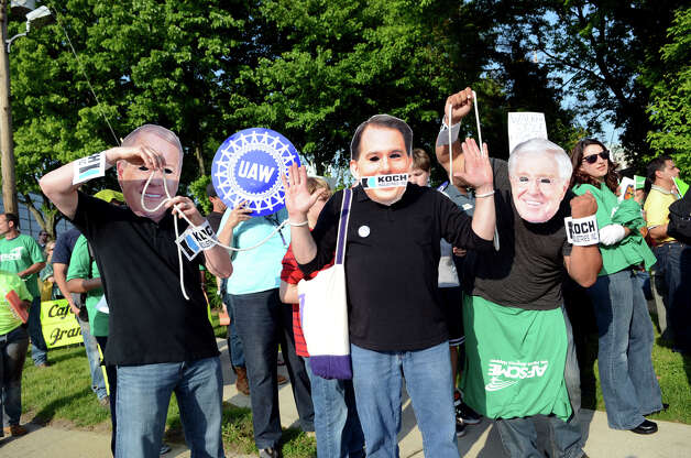 Dressed as the Koch brothers pulling the puppet strings of Wisconson Governor Scott Walker, Jeremy Zeedyk, of Cromwell, sheet metal worker Local Union 40, dressed as ; Tim Riddle, of Danbury, President Paraprofession Council; and Will Diaz, of Fairfield, AFSCME Local 714; protest the Prescott Bush Awards dinner keynote speaker Wisonsin Gov. Scott Walker across the street from the entrance to the Stamford Hilton Hotel in Stamford on Monday, May 20, 2013. Photo: Amy Mortensen / Connecticut Post Freelance
