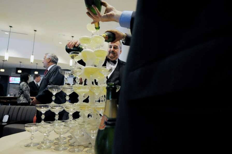 Chris Shaffer, Hilton Albany food and beverage director pours champagne over glasses stacked up duri