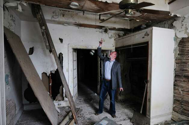 Jeff Buell, 33, points to a hole in the ceiling of 9 First Street Monday, May 20, 2013, in Troy, N.Y. Buell and Chirs Colwell were approved to purchase and rehab the property from the Troy Local Development Corporation for $10,000. (Will Waldron/Times Union) Photo: Will Waldron