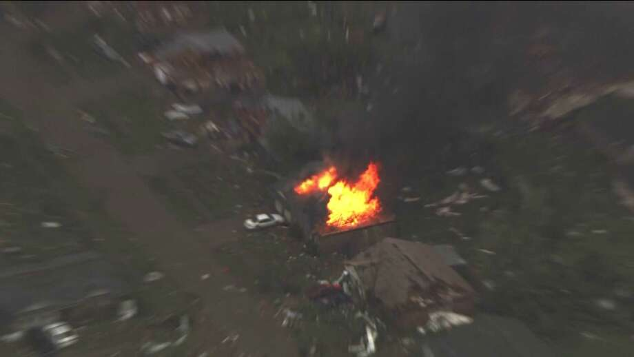 This photo provided by KFOR-TV shows a house fire outside Moore, Okla., Monday, May 20, 2013. A monstrous tornado as much as a mile wide roared through the Oklahoma City suburbs Monday, flattening entire neighborhoods, setting buildings on fire and landing a direct blow on an elementary school. (AP Photo/KFOR-TV) Photo: KFOR-TV, Associated Press / AP