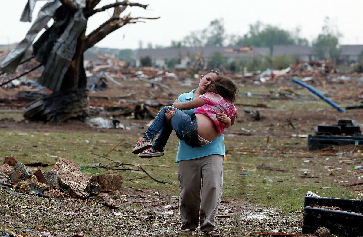 A woman carries her child through a field near the collapsed Plaza Towers Elementary School in Moore, Okla., Monday, May 20, 2013. A tornado as much as a mile (1.6 kilometers) wide with winds up to 200 mph (320 kph) roared through the Oklahoma City suburbs Monday, flattening entire neighborhoods, setting buildings on fire and landing a direct blow on an elementary school.