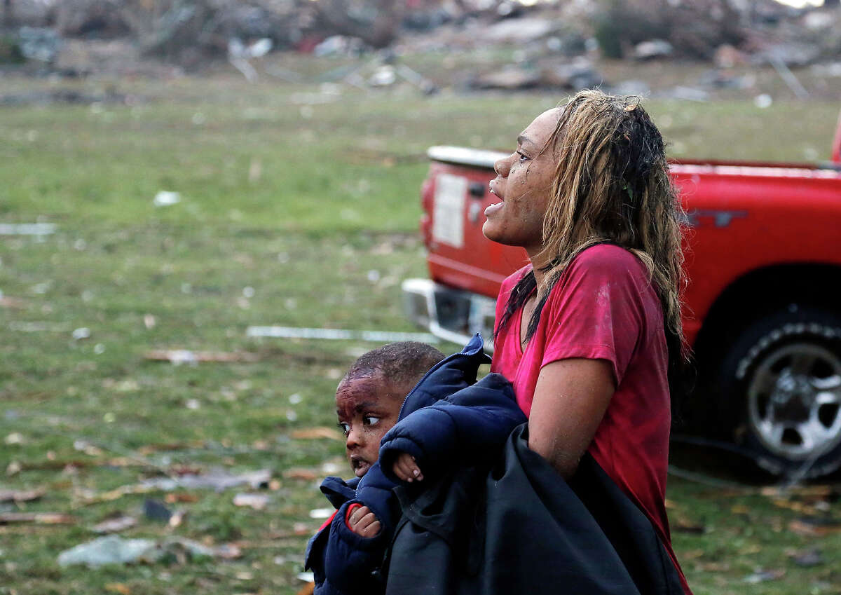 A woman carries an injured child to a triage center near the Plaza Towers Elementary School in Moore, Okla., Monday, May 20, 2013. A tornado as much as a mile (1.6 kilometers) wide with winds up to 200 mph (320 kph) roared through the Oklahoma City suburbs Monday, flattening entire neighborhoods, setting buildings on fire and landing a direct blow on an elementary school.