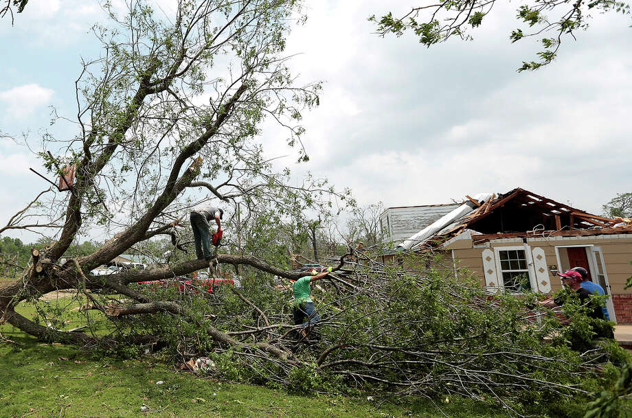Volunteers chain saw a fallen tree knocked down by a tornado May 20, 2013 near Shawnee, Oklahoma. A series of tornados moved across central Oklahoma May 19, killing two people and injuring at least 21. Photo: Brett Deering, Getty Images / 2013 Getty Images