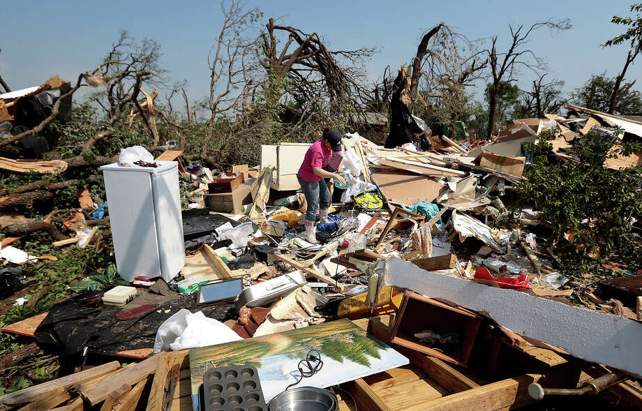 Kasey Clark sorts through the debris of her grandmother-in-law Thelma Cox's mobile home after it was destroyed by a tornado May 20, 2013 near Shawnee, Oklahoma. A series of tornados moved across central Oklahoma May 19, killing two people and injuring at least 21. Photo: Brett Deering, Getty Images / 2013 Getty Images