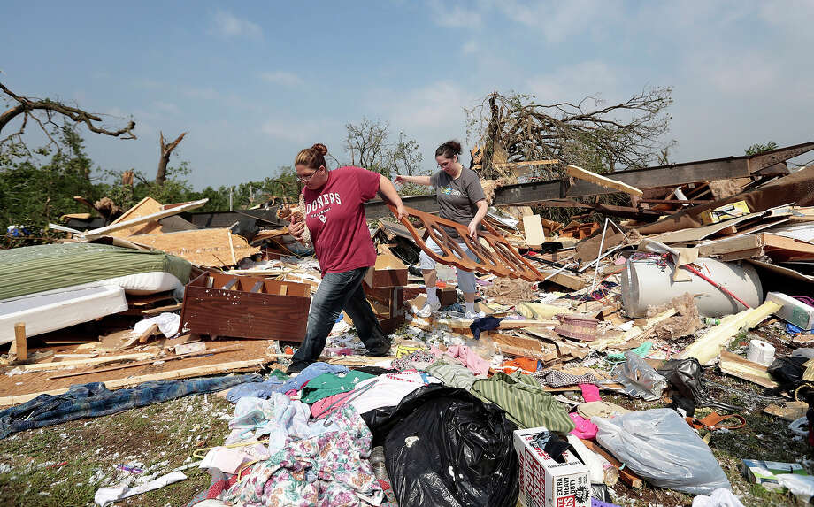 Candice Lopez (L) and Stephanie Davis help clean debris from Thelma Cox's mobile home after it was destroyed by a tornado May 20, 2013 near Shawnee, Oklahoma. A series of tornados moved across central Oklahoma May 19, killing two people and injuring at least 21. Photo: Brett Deering, Getty Images / 2013 Getty Images