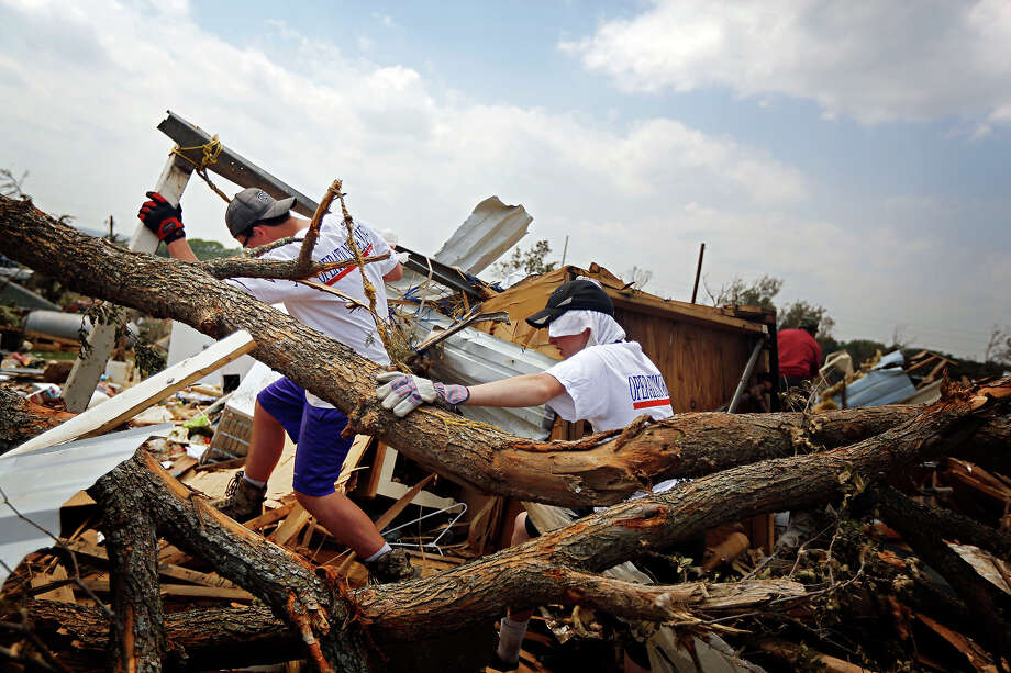Volunteers Brady Dean, left, and Sterling Offing scale the debris of a home in the Rancho Brazos subdivision Sunday, May 19, 2013 in Granbury, Texas. Residents in the neighborhood continued cleanup of their damaged homes after a May 15 tornado wreaked havoc on the area, injuring dozens and killing six people. Photo: G.J. McCarthy, ASSOCIATED PRESS / THE DALLAS MORNING NEWS2013