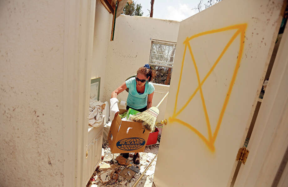 Linda Lou Wilson carries a box of debris out of the bathroom of her damaged home in the Rancho Brazos subdivision Sunday, May 19, 2013 in Granbury, Texas. Residents in the neighborhood continued cleanup of their damaged homes after a May 15 tornado wreaked havoc on the area, injuring dozens and killing six people. Wilson rode out the storm in the bathroom of the home she has lived in for 13 years. Hers was the thirteenth house built by Habitat for Humanity in the neighborhood. Photo: G.J. McCarthy, ASSOCIATED PRESS / THE DALLAS MORNING NEWS2013