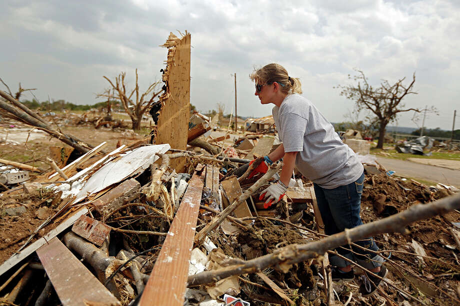 Bobi Parsons scales debris as she searches the remains of her home for valuables in the Rancho Brazos subdivision Sunday, May 19, 2013 in Granbury, Texas. Residents in the neighborhood continued cleanup of their damaged homes after a May 15 tornado wreaked havoc on the area, injuring dozens and killing six people. Photo: G.J. McCarthy, ASSOCIATED PRESS / THE DALLAS MORNING NEWS2013