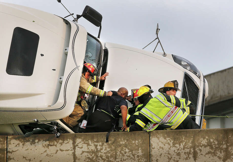 Shawnee firefighters assist driver Marco Corr as he is taken from the cab of his overturned truck, in Shawnee, Okla., Sunday, May 19,  2013. Corr was taken out of the cab through the front windshield. A tornado caused extensive damage along Interstate 40 at the junction with U.S. 177. Photo: Jim Beckel, AP / The Oklahoman