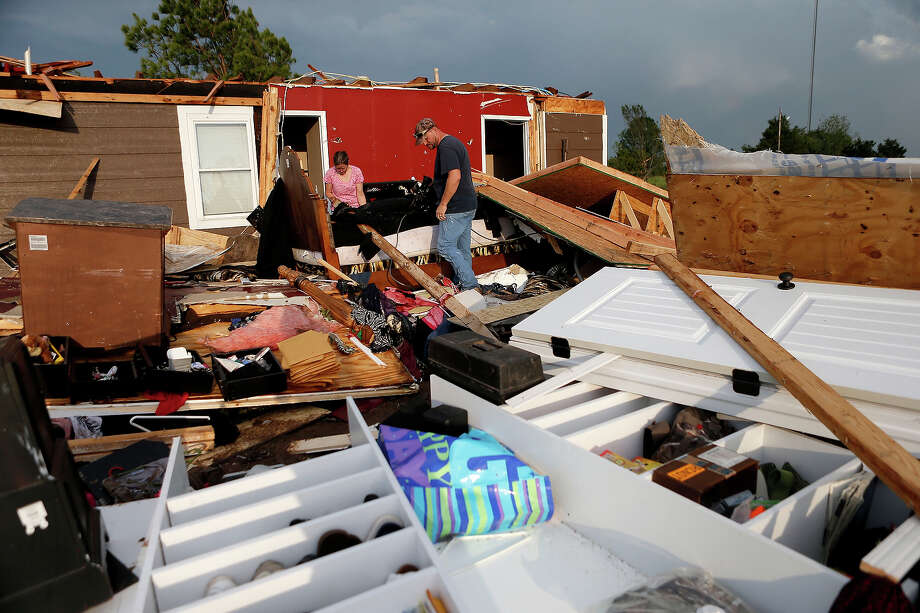 Nancy and Jason Townsend sort through belongings after their home was hit by a tornado in Carney Okla., on Sunday, May 19, 2013. The Townsend's left their home to avoid the tornado. Photo: Bryan Terry, ASSOCIATED PRESS / AP2012