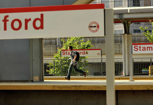 A commuter runs down a platform at the Metro-North station in Stamford on Monday, May 20, 2013. Because of the train derailment in Bridgeport, many travelers were finding the commute to and from New York City difficult. Photo: Jason Rearick / Stamford Advocate
