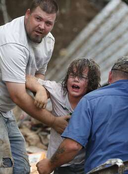 A child calls to his father after being pulled from the rubble of the Tower Plaza Elementary School following a tornado in Moore, Okla., Monday, May 20, 2013. A tornado as much as a mile (1.6 kilometers) wide with winds up to 200 mph (320 kph) roared through the Oklahoma City suburbs Monday, flattening entire neighborhoods, setting buildings on fire and landing a direct blow on an elementary school. (AP Photo Sue Ogrocki)