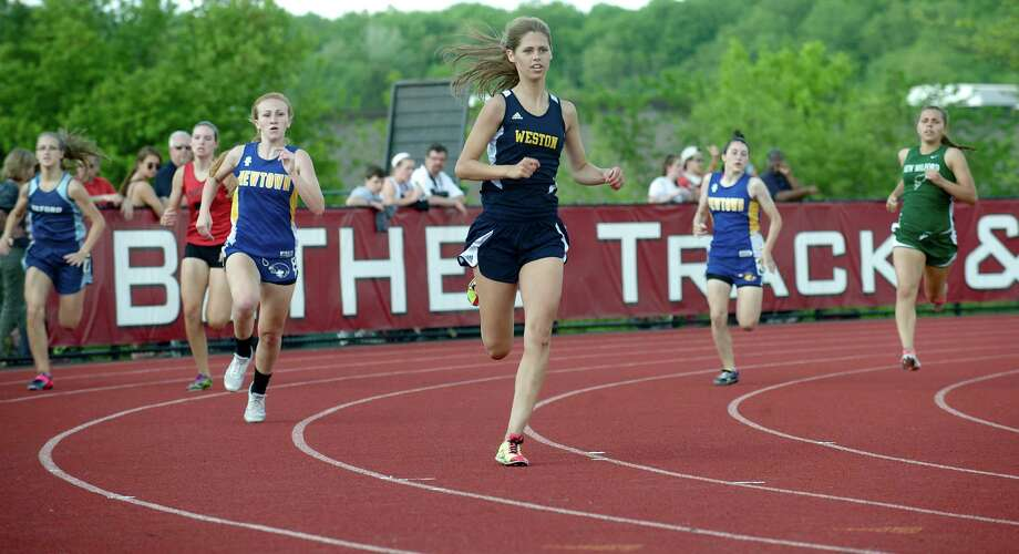 Madison Murray of Weston High School leads the girls 400 meter dash with Shelby Tolla, Newtown High School closing from behind during the South West Conference boys and girls track and field championships held at Bethel High School, Bethel, Conn. Monday May 20, 2013. Photo: H John Voorhees III