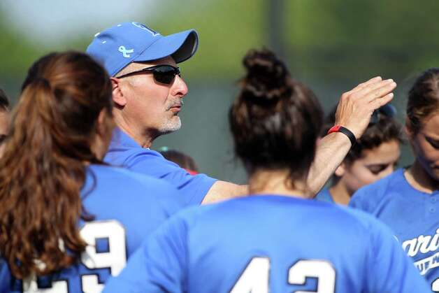 A Darien High School softball coach makes a few pointers to his team during FCIAC sofball action in Darien on Monday, May 20, 2013. Darien won the game against Greenwich, 4-1, to advance to the next round of FCIAC play. Photo: J. Gregory Raymond / Stamford Advocate Freelance;  © J. Gregory Raymond