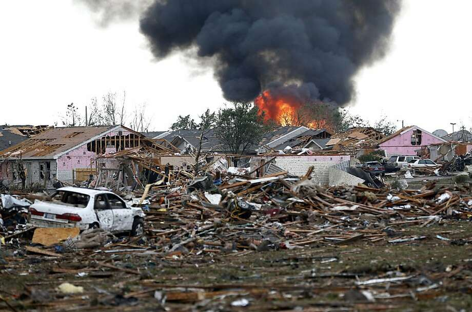 A fire burns in the Tower Plaza Addition in Moore, Okla., following a tornado Monday, May 20, 2013. A tornado as much as a mile wide with winds up to 200 mph roared through the Oklahoma City suburbs Monday, flattening entire neighborhoods, setting buildings on fire and landing a direct blow on an elementary school. (AP Photo/Sue Ogrocki) Photo: Sue Ogrocki, Associated Press