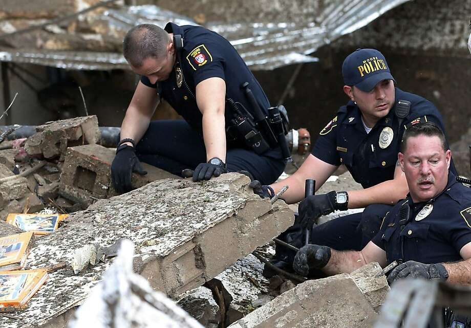 Moore police dig through the rubble of the Plaza Towers Elementary School following a tornado in Moore, Okla., Monday, May 20, 2013. A tornado as much as a mile (1.6 kilometers) wide with winds up to 200 mph (320 kph) roared through the Oklahoma City suburbs Monday, flattening entire neighborhoods, setting buildings on fire and landing a direct blow on an elementary school. (AP Photo/Sue Ogrocki) Photo: Sue Ogrocki, Associated Press