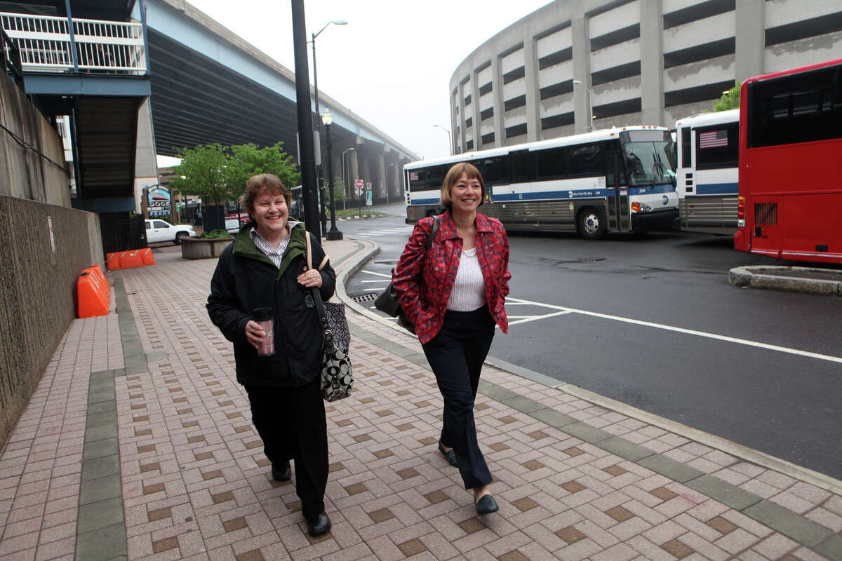 Lisa Zarny, left, and Jennifer Pascucci, both of Orange, walk to catch a bus in Bridgeport to Stamford while train service is suspended on Monday, May 20, 2013. There was no train service from Bridgeport to South Norwalk because of a train collision on Friday. Zarny and Passucci first started driving on the Merritt but got off in Bridgeport due to heavy traffic.