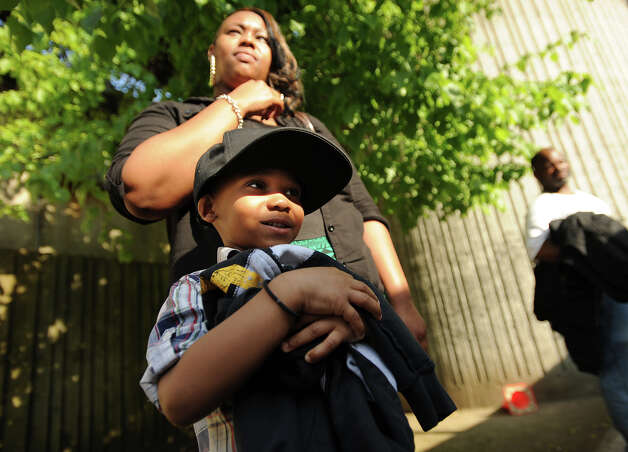 Morgan Johnson and her son Shaquan Rhodes, 5, of Stamford, wait to board a bus to South Norwalk at the Bridgeport train station in Bridgeport, Conn. on Monday, May 20, 2013. Train service is currently suspended between Bridgeport and South Norwalk due to damage caused by Friday's Metro North train derailment and collision. Photo: Brian A. Pounds / Connecticut Post
