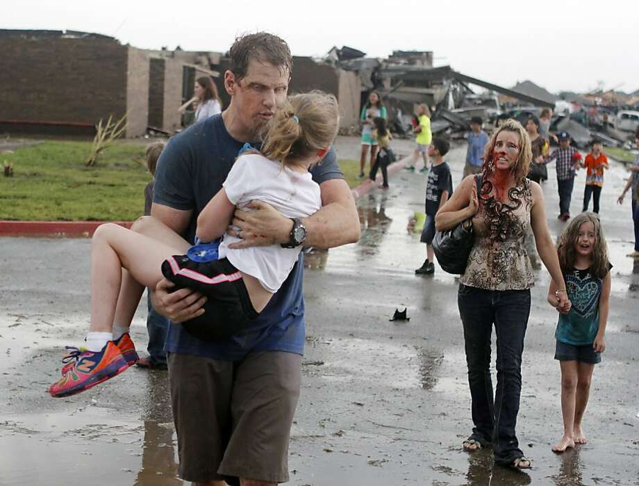 Teachers carry children away from Briarwood Elementary school after a tornado destroyed the school in south Oklahoma City, Monday, May 20, 2013. A monstrous tornado roared through the Oklahoma City suburbs, flattening entire neighborhoods with winds up to 200 mph, setting buildings on fire and landing a direct blow on an elementary school. (AP Photo/The Oklahoman, Paul Hellstern) Photo: Paul Hellstern, Associated Press