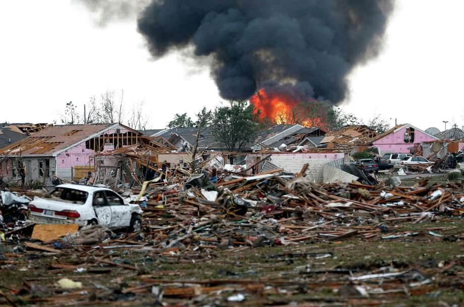 A fire burns in the Tower Plaza Addition in Moore, Okla., following a tornado Monday, May 20, 2013. A tornado as much as a mile wide with winds up to 200 mph roared through the Oklahoma City suburbs Monday, flattening entire neighborhoods, setting buildings on fire and landing a direct blow on an elementary school. (AP Photo/Sue Ogrocki) Photo: Sue Ogrocki, STF / AP