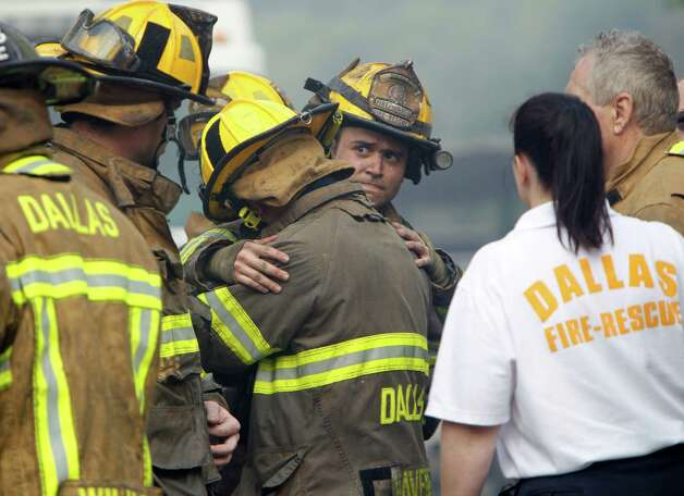 Firefighters embrace after fighting a six-alarm fire that took the life of a fellow firefighter and destroyed at least 24 units at the Hearthwood North Condominiums in Dallas, on Monday, May 20, 2013. Two other firefighters were injured in the blaze. Photo: Sonya Hebert-Schwartz, Associated Press / The Dallas Morning News