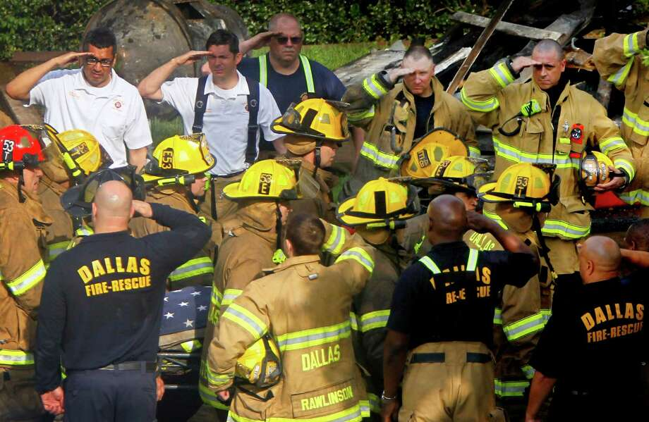 Firefighters salute as the body of a fallen firefighter is carried from the scene of a six-alarm fire that burned at least 24 units at the Hearthwood North Condominiums in Dallas, on Monday, May 20, 2013. Two other firefighters were injured in the blaze. Photo: Sonya Hebert-Schwartz, Associated Press / The Dallas Morning News