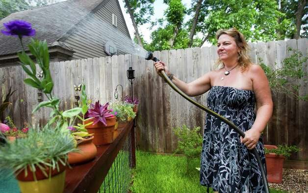 "Rindy Jones-Greer waters the plants in her backyard, Monday, May 20, 2013, in Houston. ""It's a beautiful day,"" she said. ""The wind's blowing fine, and the heat's not on yet."" She waters her plants everyday unless it rains. Photo: Cody Duty, Houston Chronicle / © 2013 Houston Chronicle"