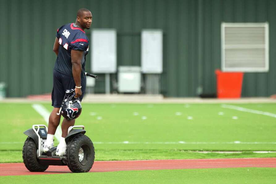 Houston Texans defense end Antonio Smith rides a Segway across the practice field before Texans' Org