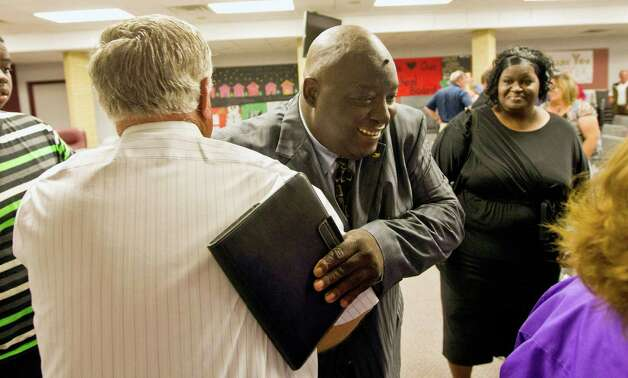Sidney Johnson, facing, gets a hug from Waller City Mayor Danny Marburger after his first day as a Waller City Councilman, Monday, May 20, 2013, in the Waller Independent School District building in Waller. Johnson, who's instrumental in Federal probes to clear up corruption, is the first African American to be elected to Waller City Council. Photo: Nick De La Torre, Chronicle / © 2013 Houston Chronicle