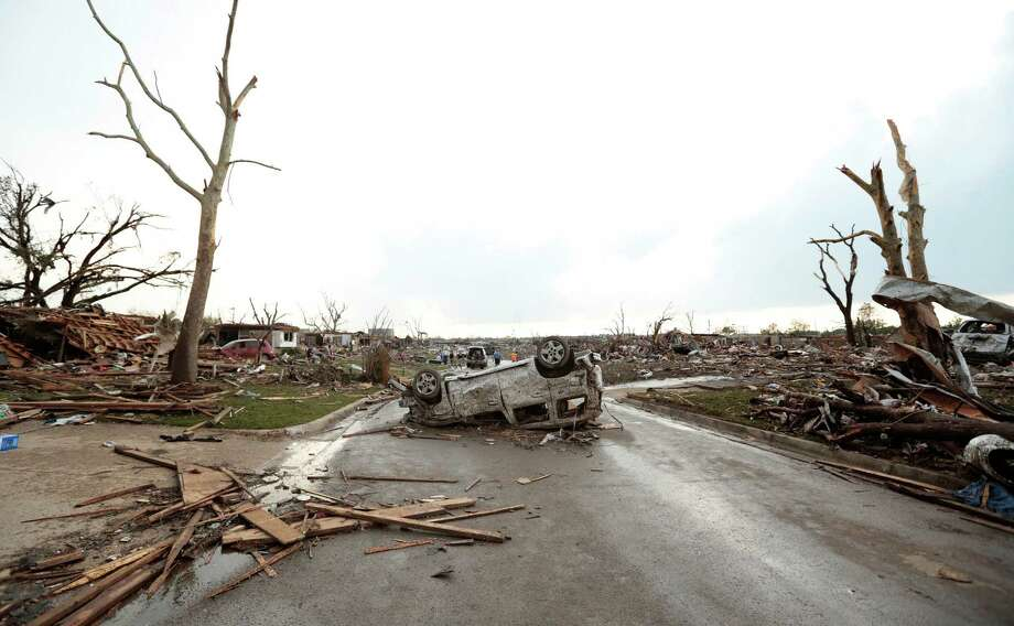 A vehicle lies upside down in the road after a powerful tornado ripped through the area on May 20, 2013 in Moore, Oklahoma. The tornado, reported to be at least EF4 strength and two miles wide, touched down in the Oklahoma City area on Monday killing at least 51 people. Photo: Brett Deering, Getty Images / 2013 Getty Images