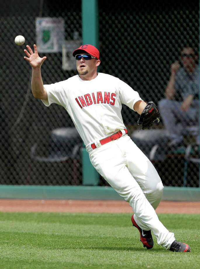 Cleveland Indians' Ryan Raburn bare hands the ball hit by Seattle Mariners' Brendan Ryan in the seventh inning of a baseball game, Monday, May 20, 2013, in Cleveland. Ryan was safe at first base.  (AP Photo/Tony Dejak) Photo: Tony Dejak