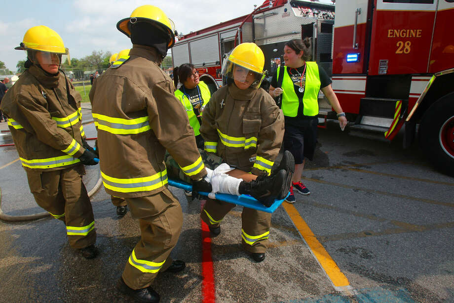 Edison High School students carry an actor playing a victim during the mass-casualty exercise at the high school. Photo: John Davenport / San Antonio Express-News