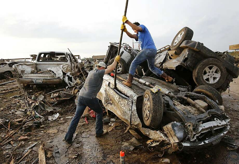 Two men attempt  to pry open a door on this car to check for victims in a business parking lot west of I-35 south of 4th Street  in Moore, on Monday, May 20, 2013.A monstrous tornado roared through the Oklahoma City suburbs, flattening entire neighborhoods with winds up to 200 mph, setting buildings on fire and landing a direct blow on an elementary school. (AP Photo/The Oklahoman, Jim Beckel) Photo: Jim Beckel, Associated Press