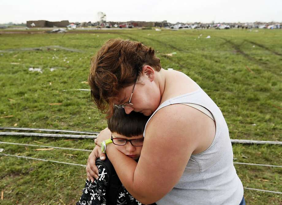 Rebekah Stuck hugs her son, Aiden Stuck, 7, after she found him in front of the destroyed Briarwood Elementary after a tornado struck south Oklahoma City and Moore, Okla., Monday, May 20, 2013. Aiden Stuck was inside the school when it was hit. (AP Photo/ The Oklahoman, Nate Billings) Photo: Nate Billings, Associated Press