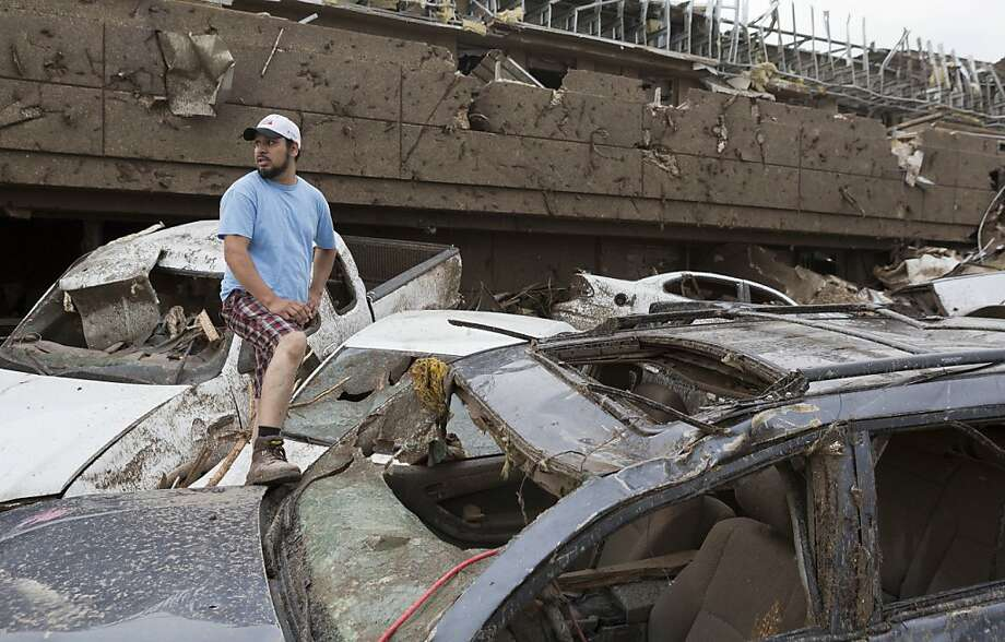 Antonio Flores of Moore, Okla. searches for his car after a tornado damaged the Moore Medical Center and the vehicles in the parking lot in Moore, Okla. on Monday, May 20, 2013. (AP Photo/Alonzo Adams) Photo: Alonzo Adams, Associated Press
