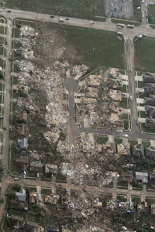 This aerial photo shows the remains of homes hit by a massive tornado in Moore, Okla., Monday May 20, 2013. A tornado roared through the Oklahoma City suburbs Monday, flattening entire neighborhoods, setting buildings on fire and landing a direct blow on an elementary school. (AP Photo/Steve Gooch) Photo: Steve Gooch, Associated Press