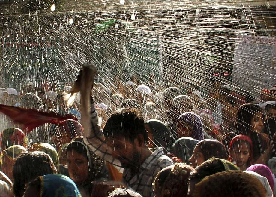 Devotees are showered with perfumed water during the end of the Urs festival, at the shrine of Sufi saint Khwaja Moinuddin Chishti in Ajmer, India, Monday, May 20, 2013. Thousands of Sufi devotees from different parts of India travel to the shrine for the annual festival, marking the death anniversary of the saint. (AP Photo/ Deepak Sharma) Photo: Deepak Sharma, Associated Press