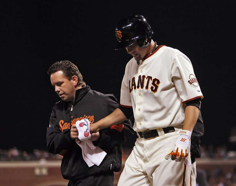 Assistant trainer Mark Gruesbeck helps Ryan Vogelsong off the field. Photo: Carlos Avila Gonzalez, The Chronicle