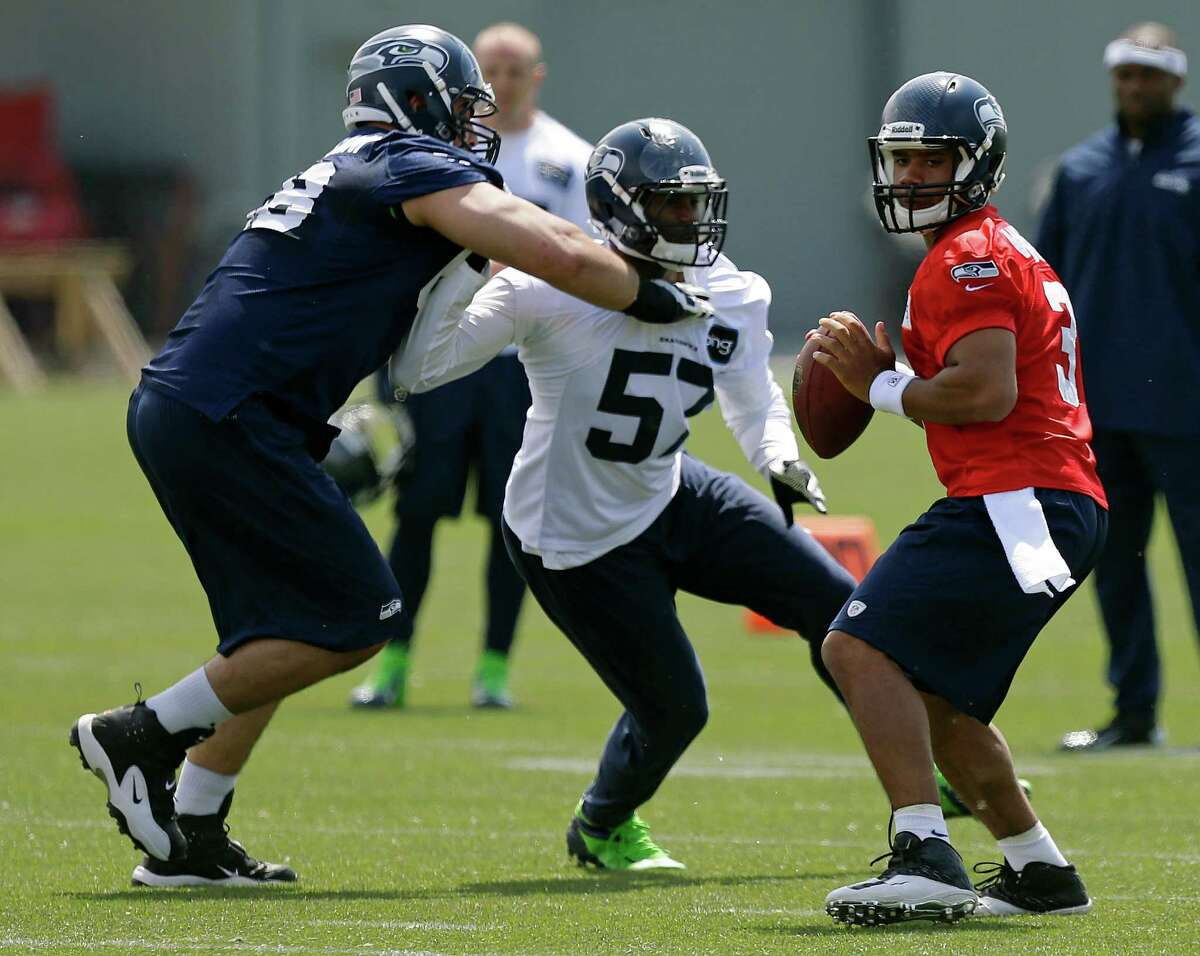 Seattle Seahawks quarterback Russell Wilson, right, looks to pass as Seahawks' Mike Morgan (57) is blocked by Seahawks' Breno Giacomini, left, Monday, May 20, 2013, during an organized team activity workout in Renton, Wash. (AP Photo/Ted S. Warren)