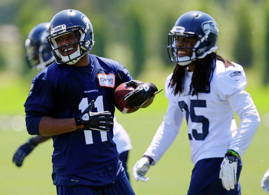 Seattle Seahawks new wide receiver Percy Harvin (11) laughs with teammate Richard Sherman, right, following a play Monday, May 20, 2013, during an NFL football organized team activity workout in Renton, Wash. (AP Photo/Ted S. Warren) Photo: Associated Press