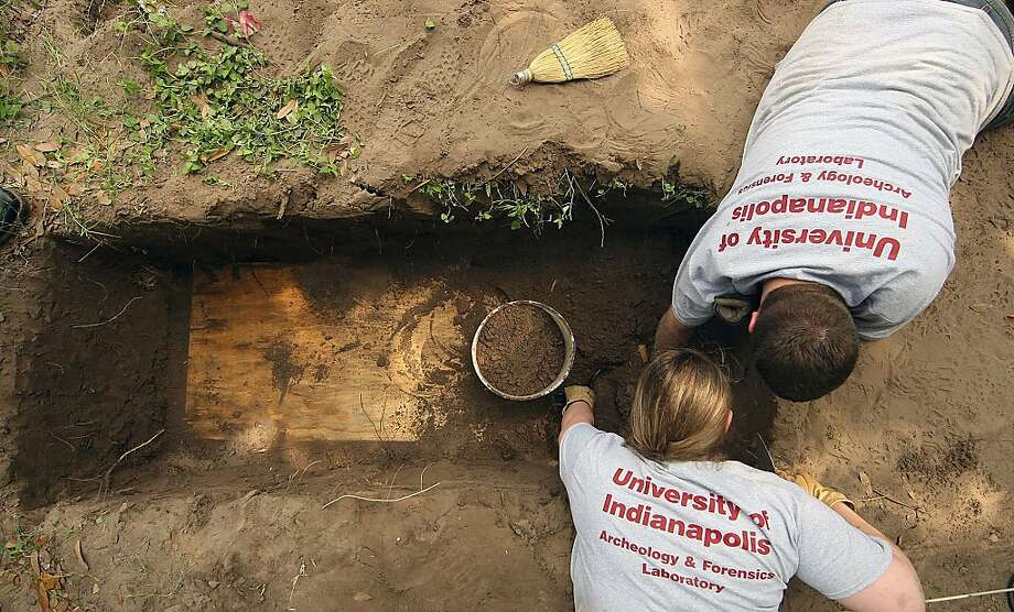 Jessica Campbell and Justin Maiers (bottom to top) with the University of Indianapolis archeology & forensics laboratory dug up a casket at the Sacred Heart Burial Park in Falfurrias,Texas, Monday, May 20, 2013. The casket contained the body of the illegal immigrants who died while trying to cross Brooks County. (AP Photo/Corpus Christi Caller-Times, Todd Yates) MANDATORY CREDIT, TV OUT, MAGS OUT Photo: Todd Yates, Associated Press