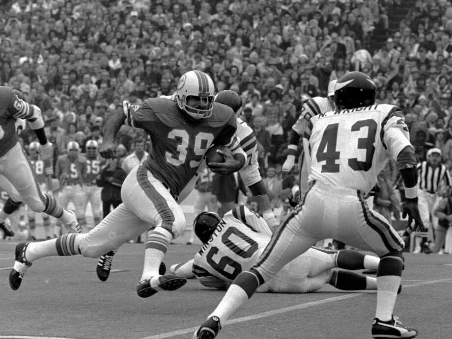 Dolphins running back Larry Csonka (39) breaks a tackle attempt by Vikings Roy Winston (60) and Nate Wright (43) in the first quarter. Photo: HTW, AP