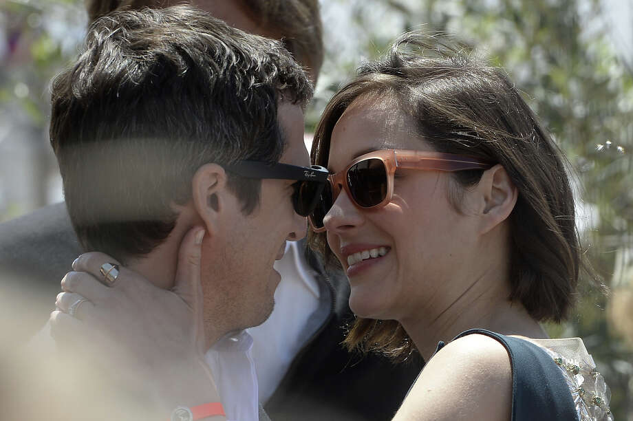 "French actress Marion Cotillard (R) hugs her partner French director Guillaume Canet on May 20, 2013 before attending a photocall for the film ""Blood Ties"" presented Out of Competition at the 66th edition of the Cannes Film Festival in Cannes. Cannes, one of the world's top film festivals, opened on May 15 and will climax on May 26 with awards selected by a jury headed this year by Hollywood legend Steven Spielberg. Photo: ANNE-CHRISTINE POUJOULAT, AFP/Getty Images / 2013 AFP"
